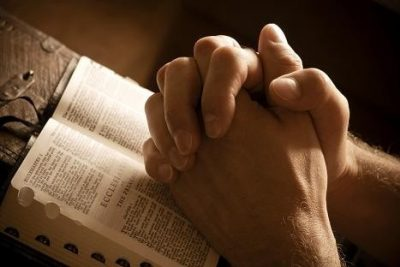 Hands closed in prayer on an open bible